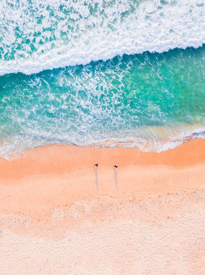 beach desktop wallpaper waves crashing into the sandy beach two people walking on the beach photographed from above