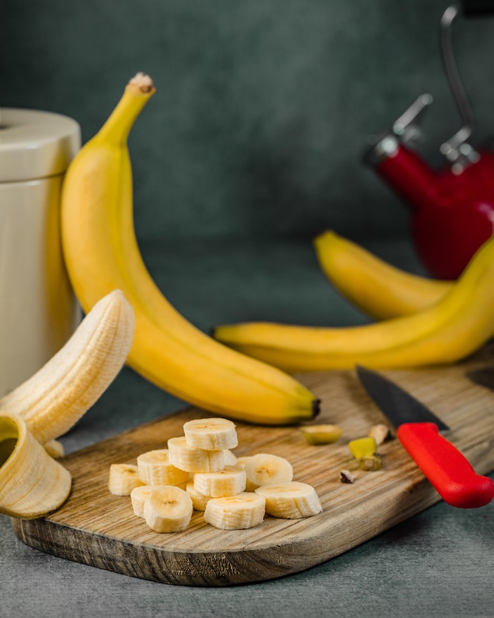 best hair mask for dry hair banana chopped up on wooden cutting board other bananas around it on table