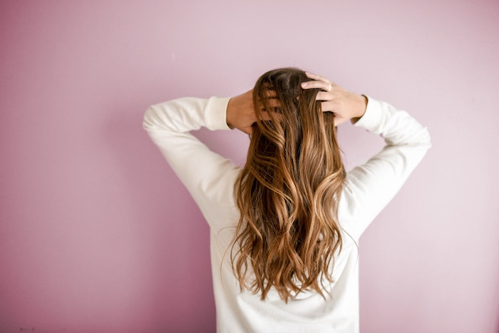 best hair mask woman with long light brown caramel wavy hair wearing white blouse pink background