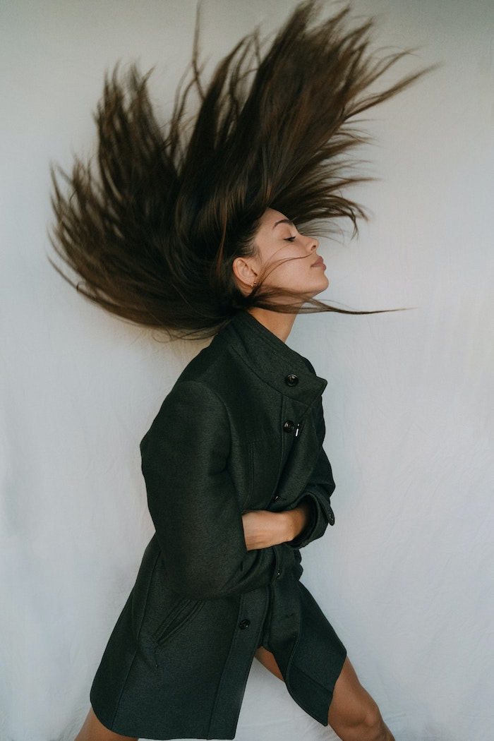 black coat worn by woman flipping her long brunette hair back hair mask for curly hair