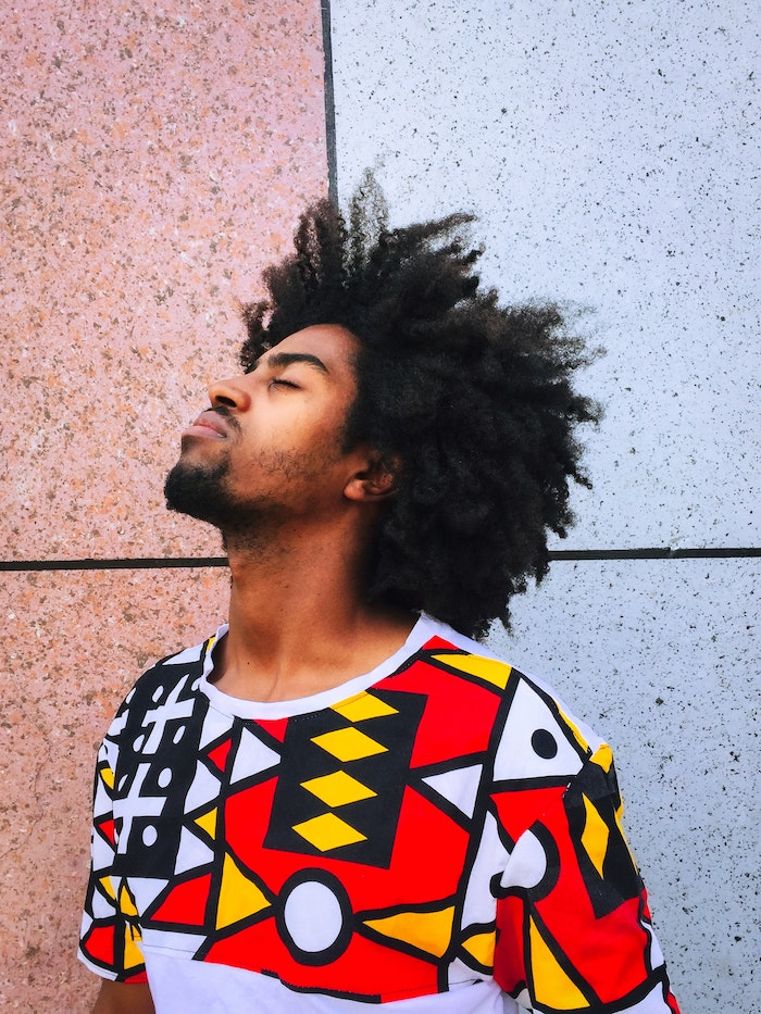 black curly hair on man wearing colorful t shirt diy deep conditioner standing in front of granite tiled wall