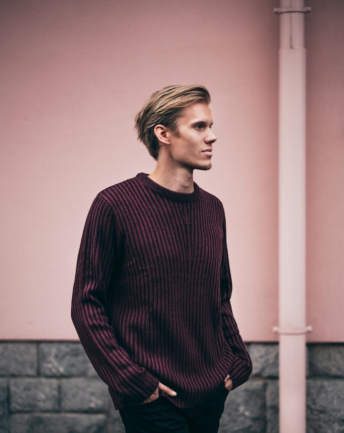 blonde man photographed on the street hair mask for curly hair wearing dark purple sweater black jeans