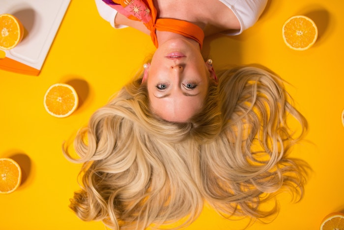 blonde woman laying on yellow surface hair spread out homemade hair mask lemons around her