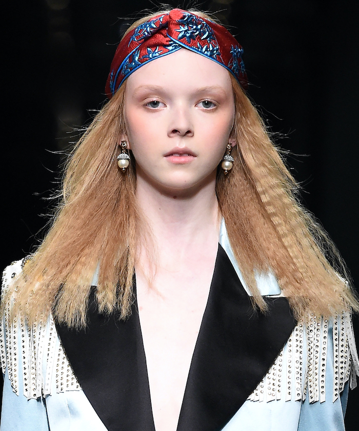blonde-woman-wearing-blue-jacket-crimped-bob-head-scarf-on-her-head-in-red-and-blue
