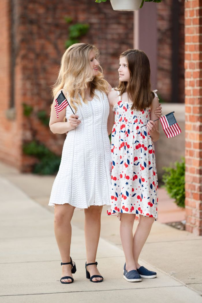 blonde woman wearing white lace dress girl wearing red white and blue dress baby boy 4th of july outfit holding american flags
