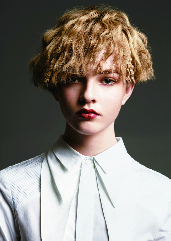 blonde woman with short crimped hair wearing white shirt red lipstick phootographed on black background