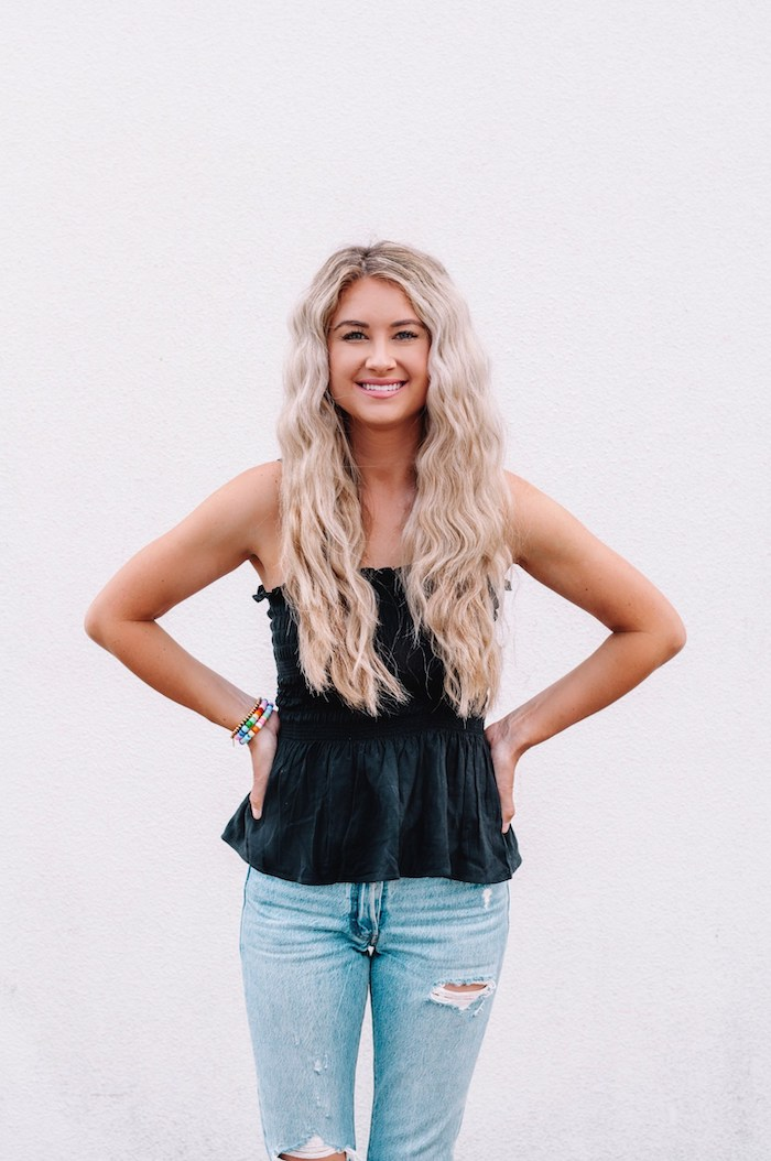 blonde woman with very long hair crimped hair 90s wearing jeans and black top