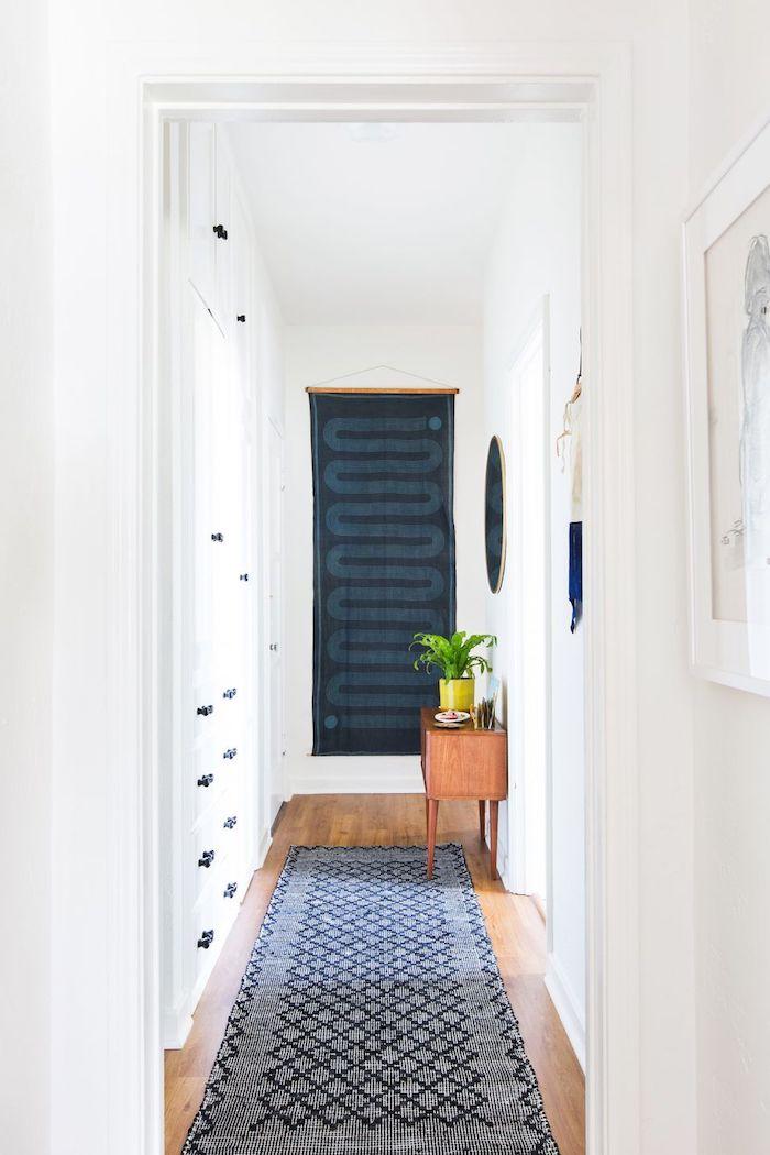 blue fabric art hanging on white walls hallway wall decor blue rug on wooden floor wooden cupboard