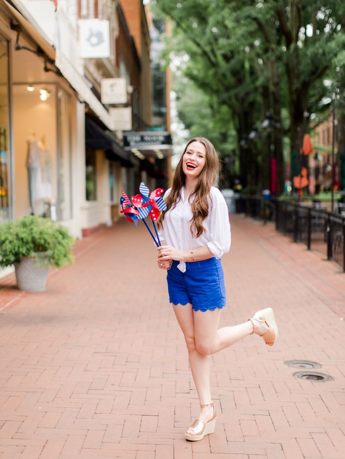 blue shorts white blouse platform sandals 4th of july clothes worn by woman with long hair