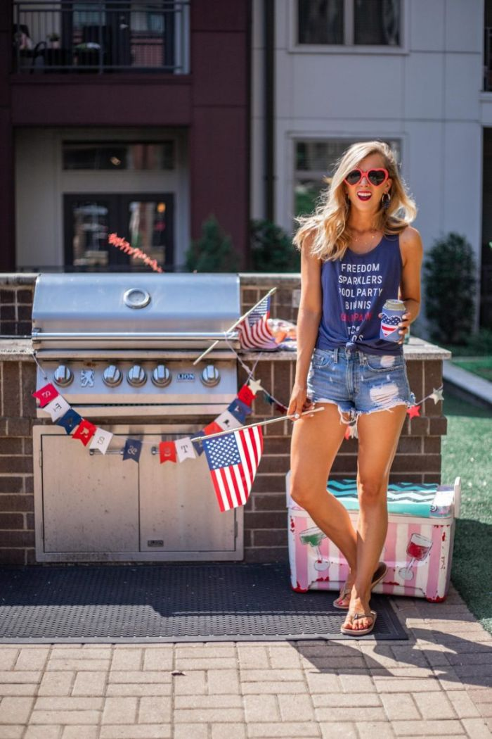 blue top denim shorts worn by blonde woman 4th of july clothes standing next to grill