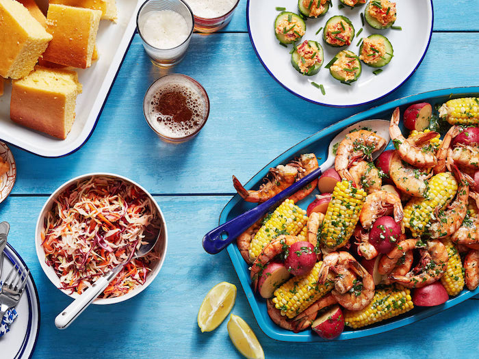 blue wooden table seafood boil sauce plate filled with shrimp corn on the cob potatoes coleslaw salad on the side