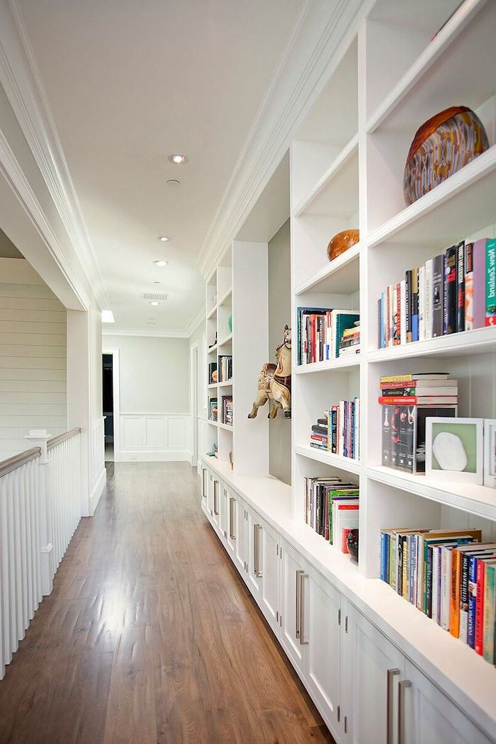 bookcase along the length of the hallway with white shelves cupboards entry way decorating ideas wooden floor
