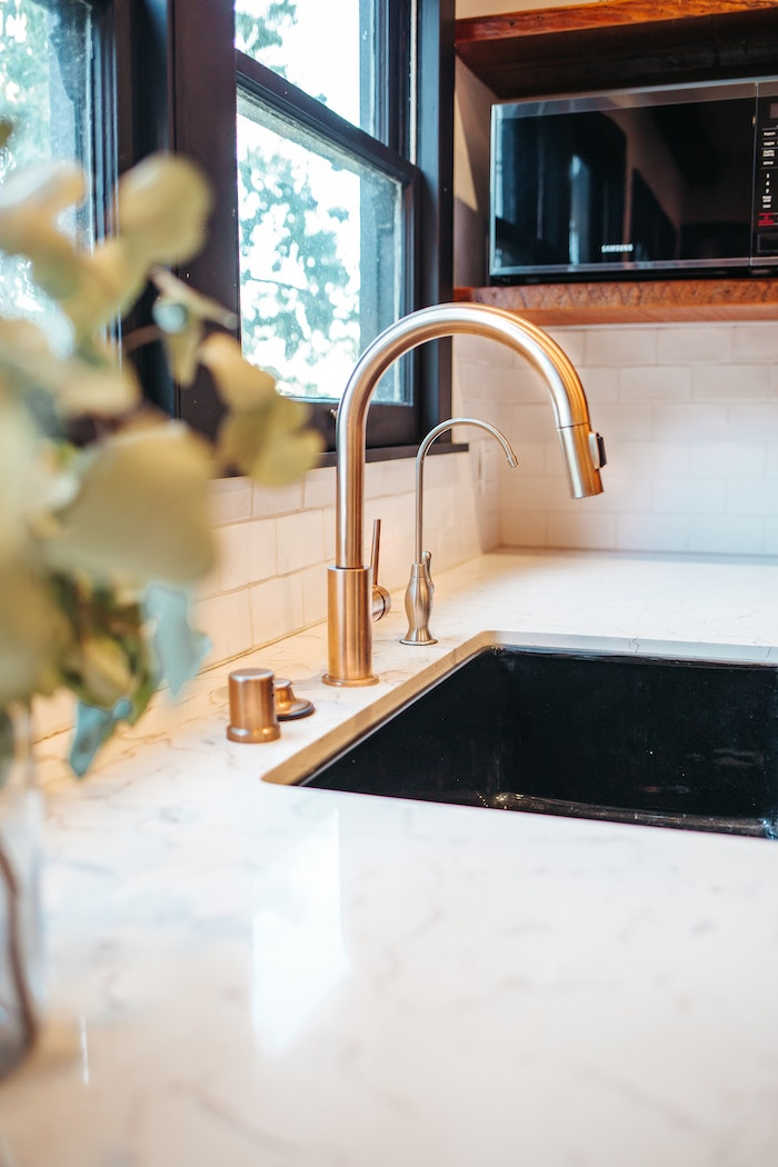 brass tap marble countertop black sink professional plumbing services