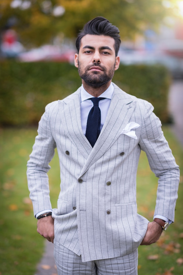 brunette man wearing gray suit with blue tie coconut oil hair mask short black hair beard