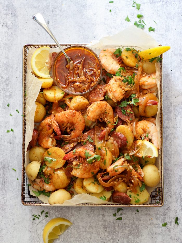 cajun seafood boil paper lined baking sheet filled with shrimp potatoes lemon wedges sauce in a bowl on the side