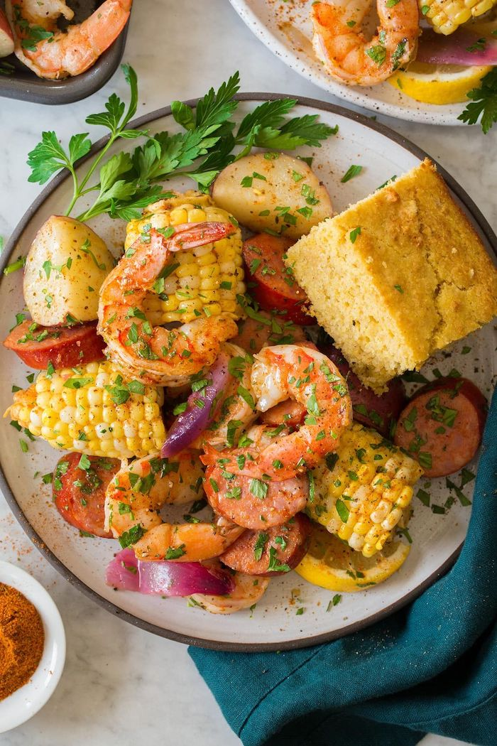cajun seafood boil recipe shrimp boil with potatoes sausages corn on the cob garnished with fresh parsley
