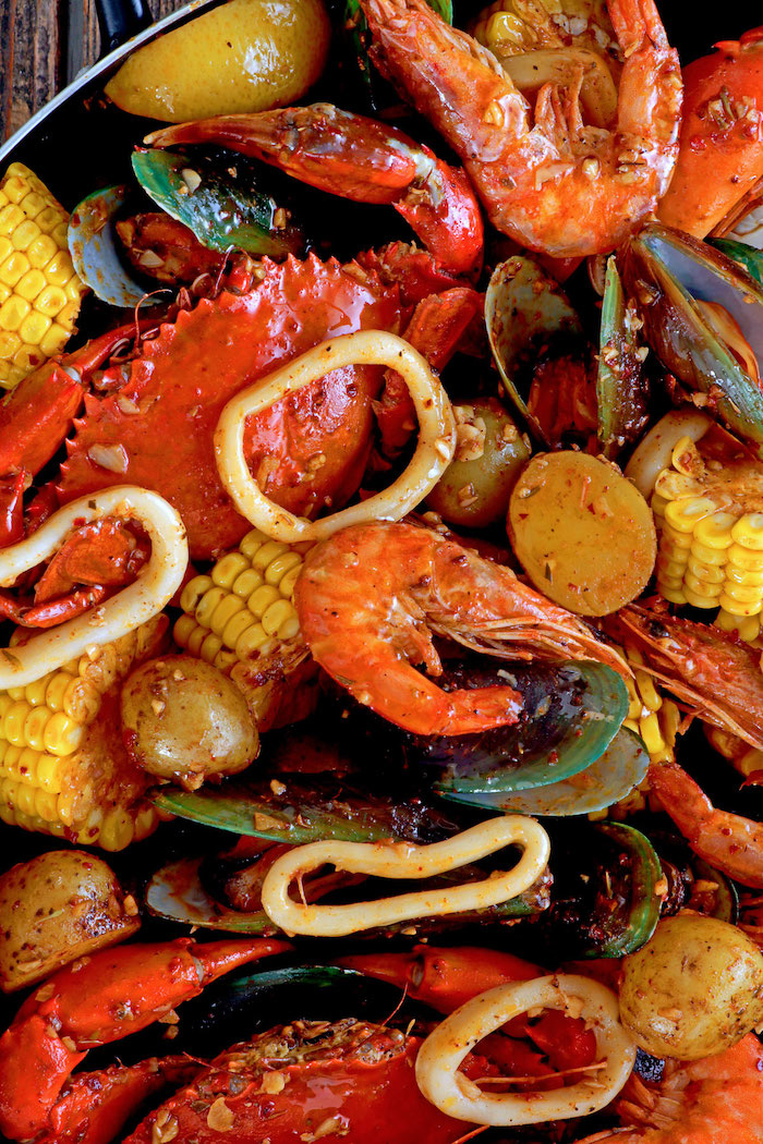 close up photo of cajun seafood boil with crabs shrimp mussels corn potatoes squid rings