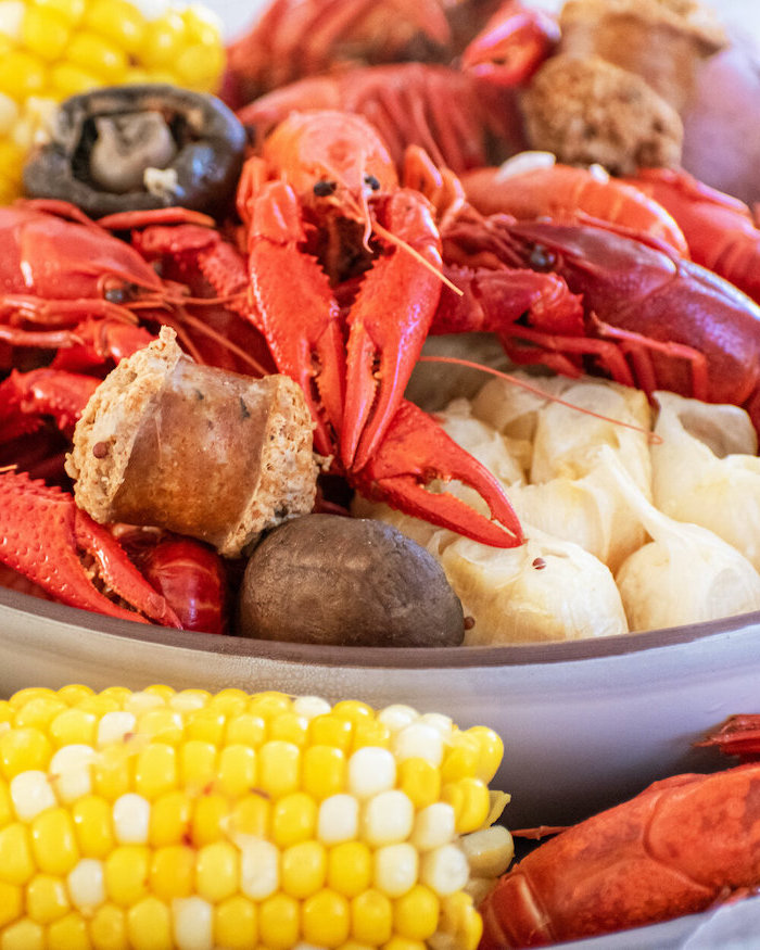 close up photo of crawfish boil how to make a seafood boil with sausages garlic onion potatoes corn on the cob