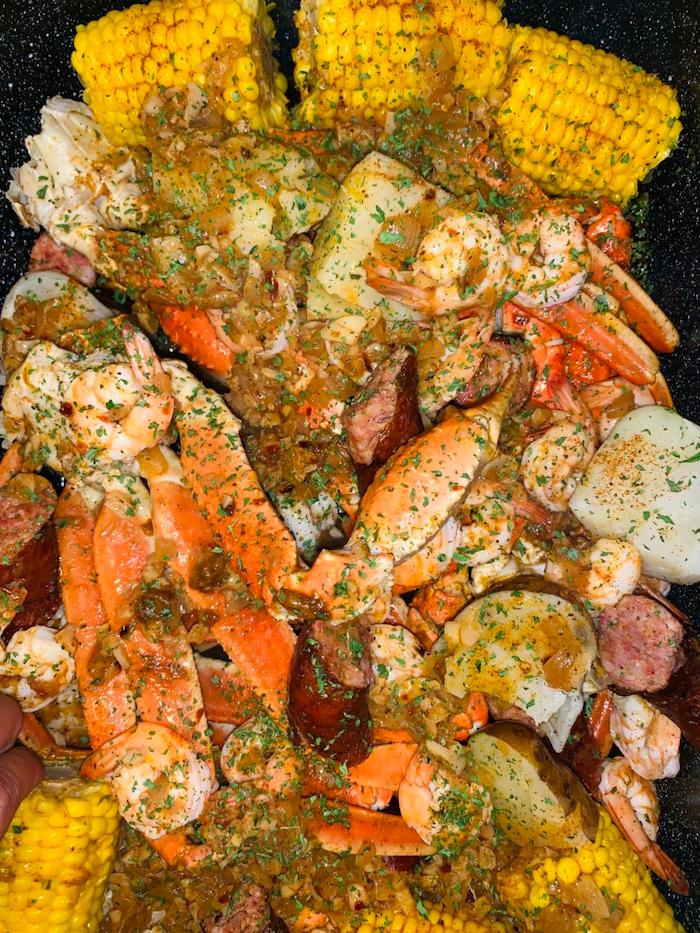 close up photo of how to make a seafood boil corn on the cob sausages potatoes garnished with chopped parsley