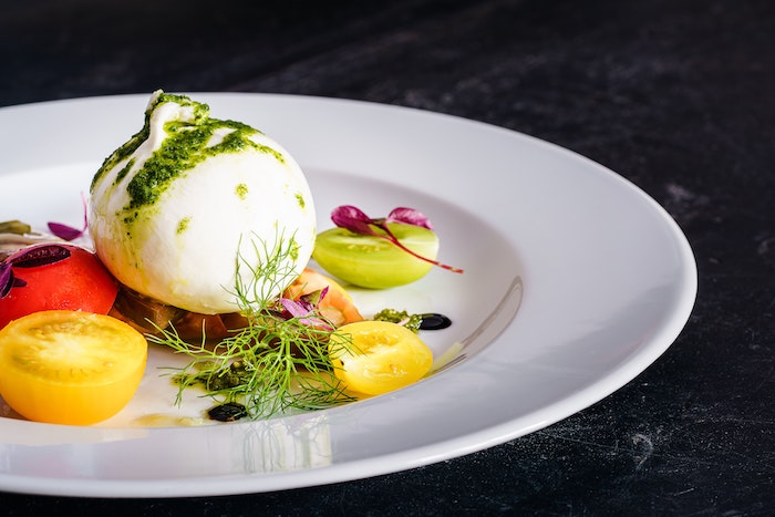 colorful cherry tomatoes on white plate italian burrata cheese drizzled with pesto sauce