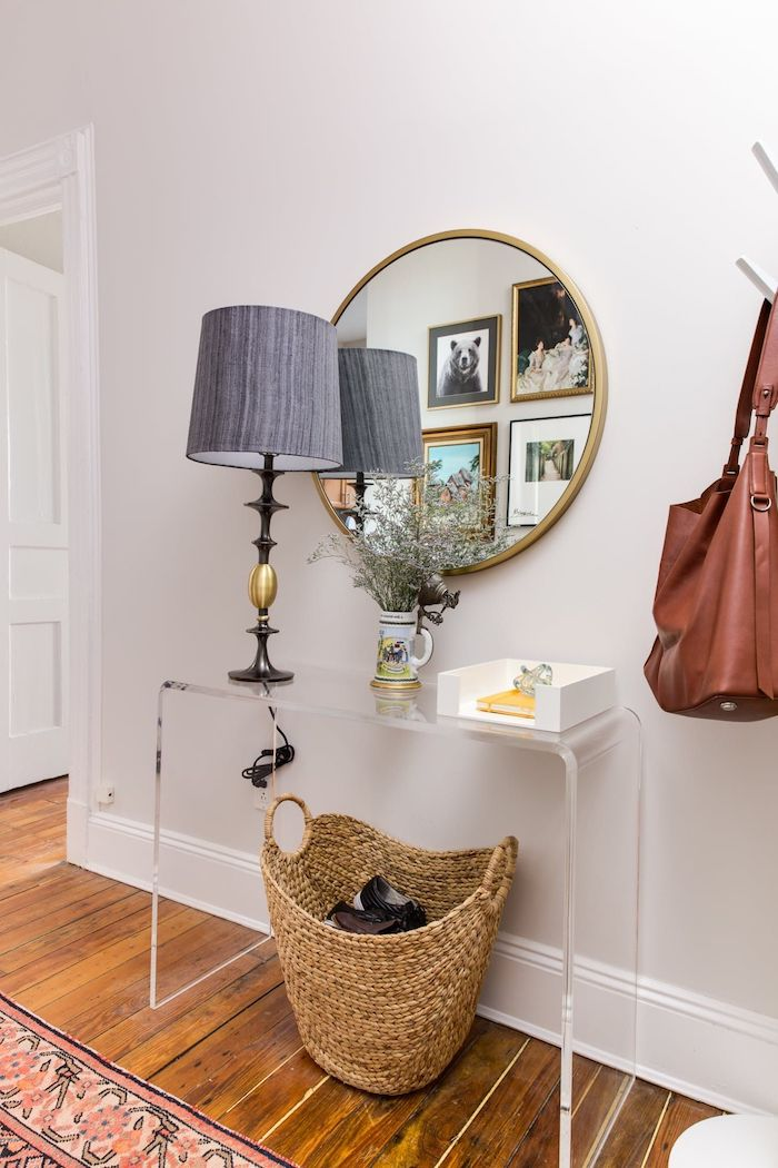 colorful rug on the floor entryway wall decor round mirror hanging on white wall above plastic shelf gray lamp on it