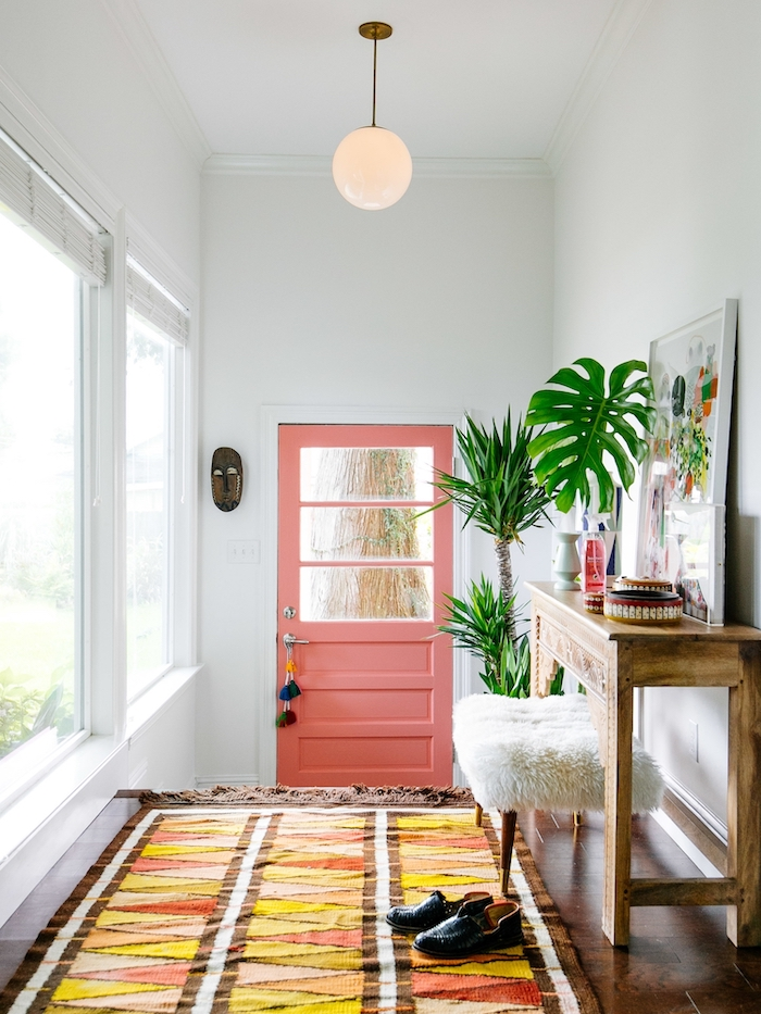 colorful rug on wooden floor decorating ideas for stairs and hallways pink door white walls tall windows framed art potted plants boho style