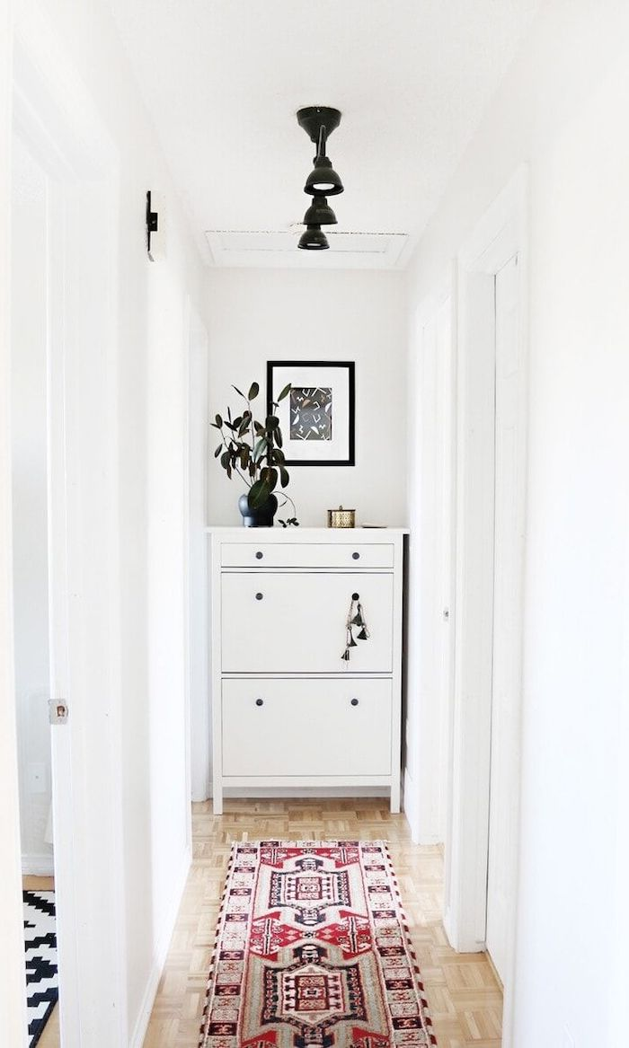 colorful rug on wooden floor narrow hallway ideas white cupboard at the end black light fixtures