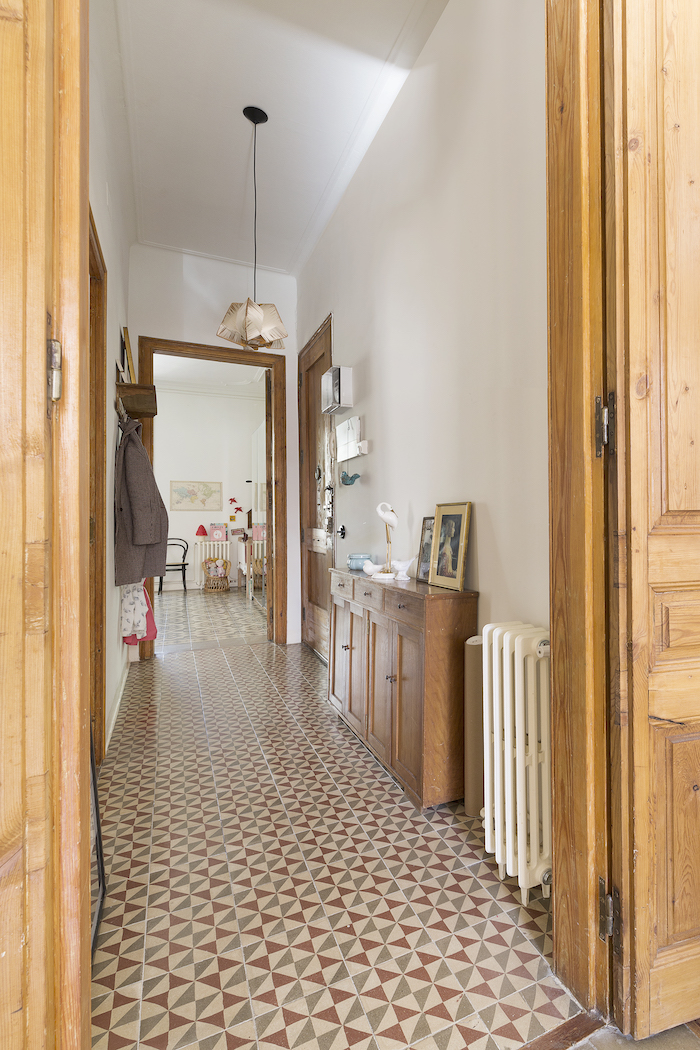 colorful tiles on the floor white walls wooden walls doors and cupboard entryway wall decor framed art on it