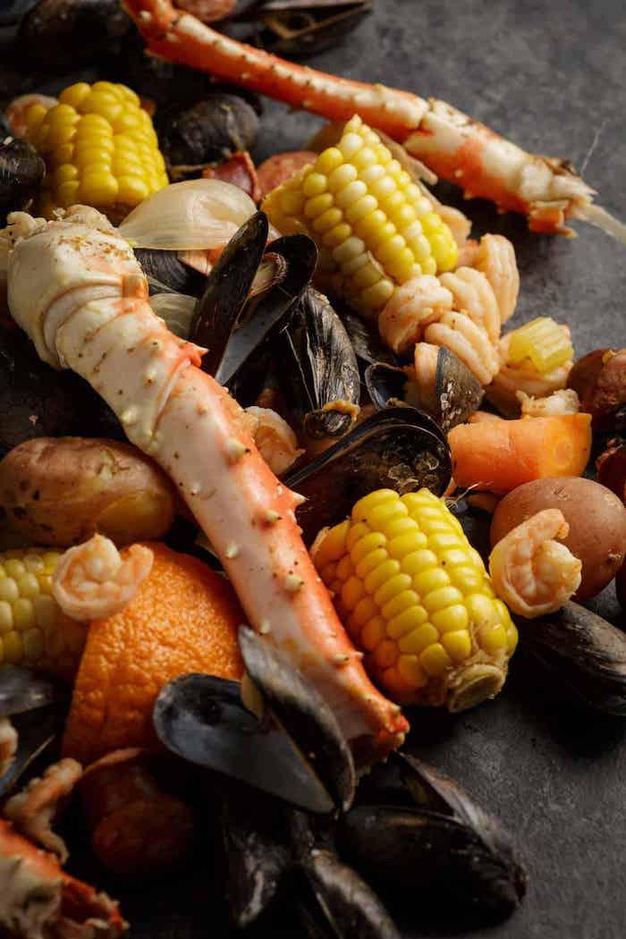 corn mussels shrimp crab boil seasoning potatoes carrots placed on black surface