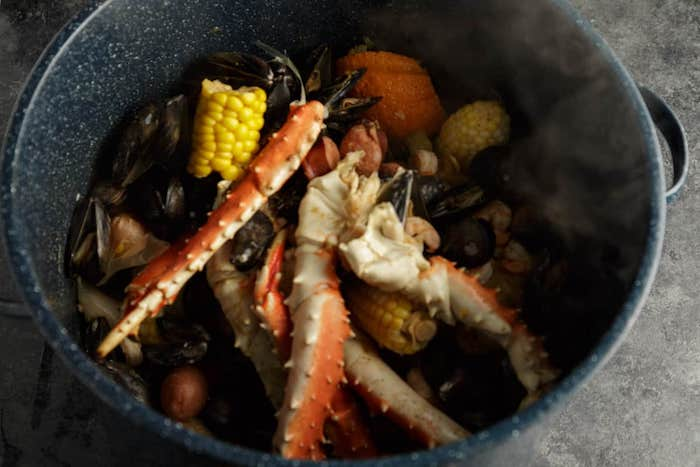 crab boil seasoning with corn mussels potatoes all placed in pan in boiling water