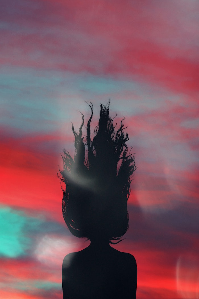 creative photo of shadow of woman with her hair up in the air best hair mask for damaged hair colorful background