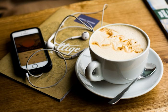 cup of coffee placed on wooden table lifestyle podcast examples phone next to it with plugged in headphones