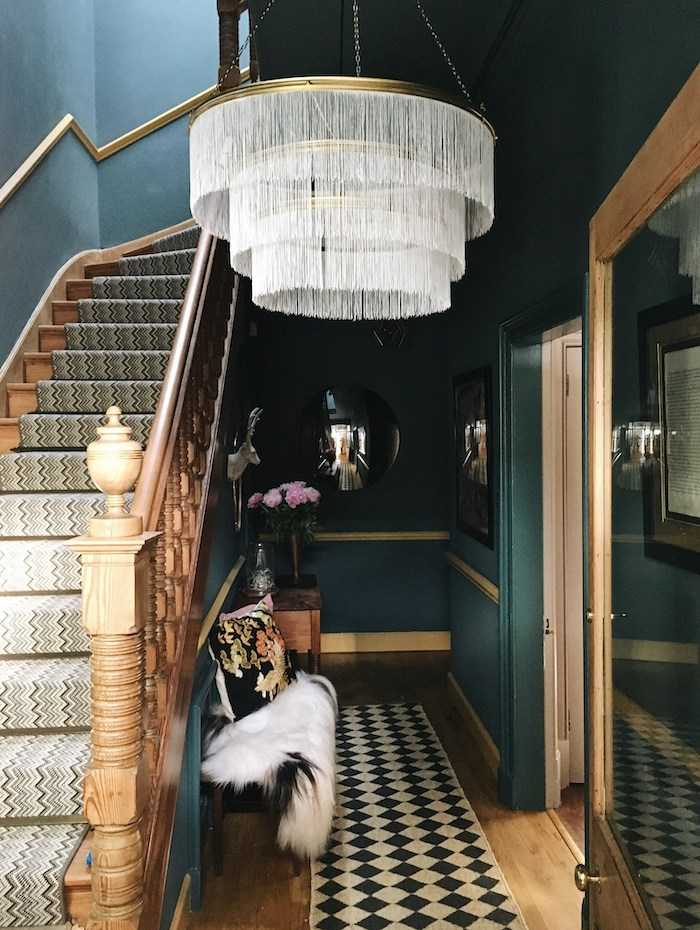 dark green walls large chandelier decorating ideas for stairs and hallways blue and white rug on staircase and wooden floor