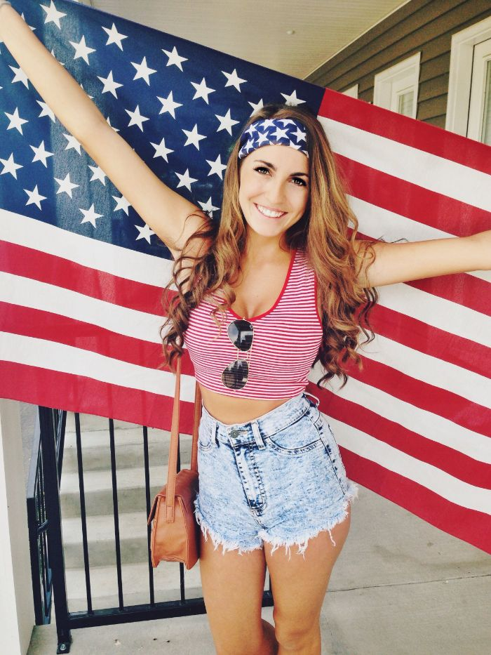 denim shorts red and white striped top worn by woman holding the american flag fourth of july outfits