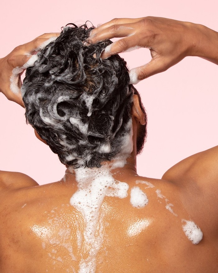 diy hair mask man under the shower rubbing shampoo on his hair pink background