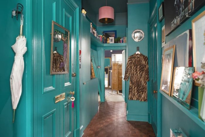 entryway wall decor turquoise walls and doors with open shelving lots of framed art and books on the walls