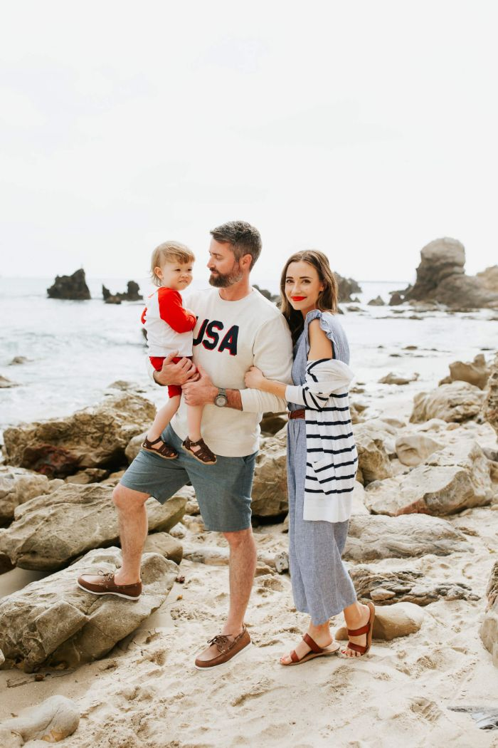 family of three standing on the beach 4th of july outfits dad wearing usa blouse