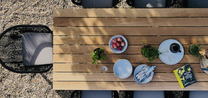 farmhouse garden table wooden table with bowl full of apples potted plants white plates on it chairs around it