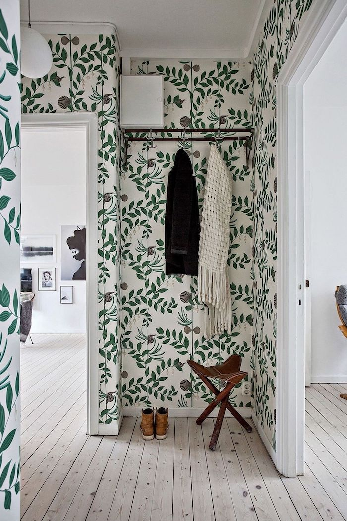 floral wallpaper with green leaves light wooden floor entryway decor black metal hangers