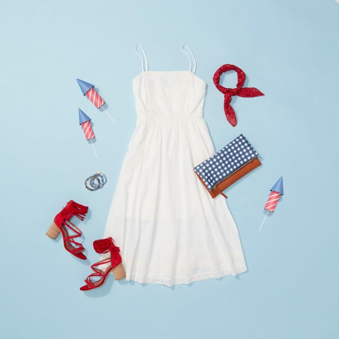fourth of july shirts white dress red sandals blue and white leather bag layed out on blue surface