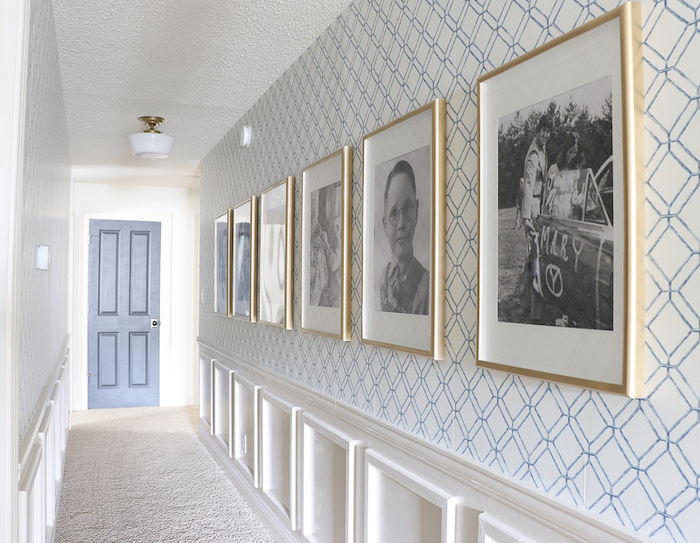 framed art on wall covered with geometrical wallpaper in blue and white hallway wall decor blue door at the end