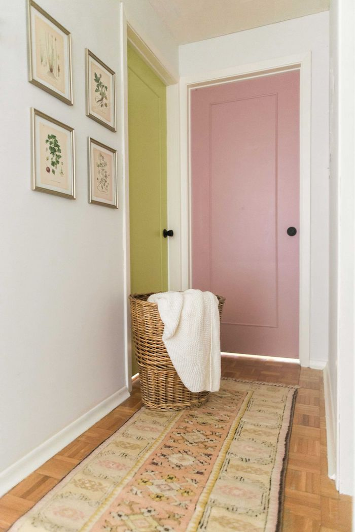 green and pink doors white walls entryway wall decor framed art on the wall colorful rug on the wooden floor