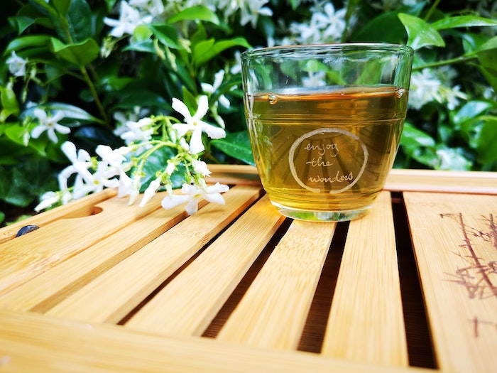 green tea inside glass placed on wooden surface home remedies for dry hair white flowers around it