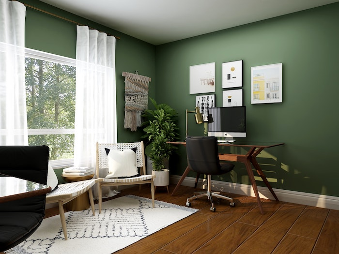 green walls in home office working from home desk with black leather chair mac computer on it
