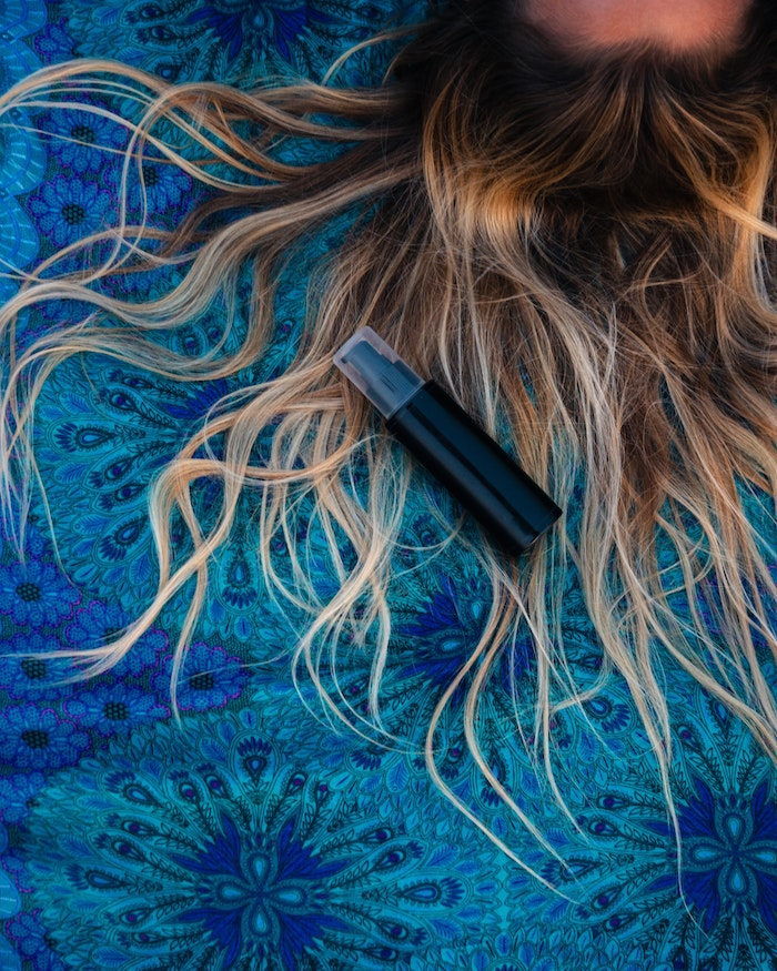 hair with balayage spread out on surface covered with blue blanket diy hair mask spray bottle placed on it