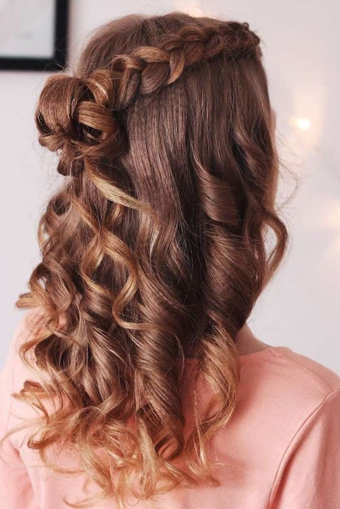 half of the hair braided on the side tied in small bun 80s crimped hair woman wearing pink blouse