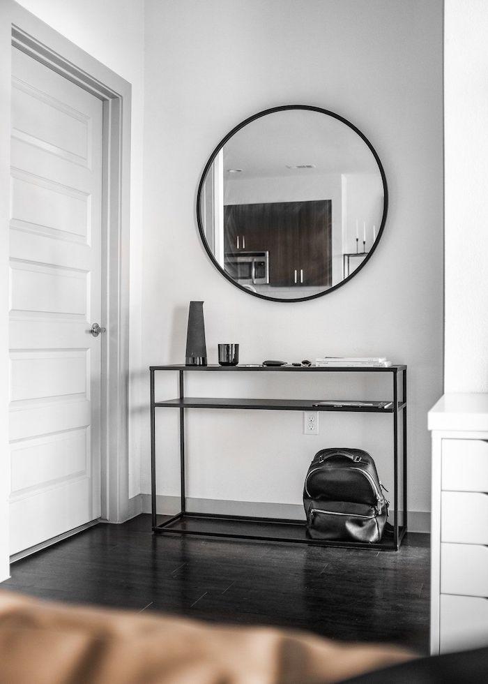 hallway decor ideas white walls black wooden floor round mirror above open shelf cupboard with black metal frames