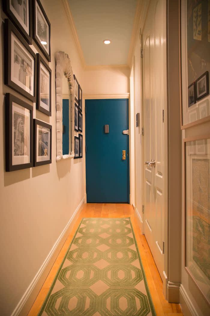 hallway wall decor ideas blue door white walls green rug on the wooden floor framed art on the walls