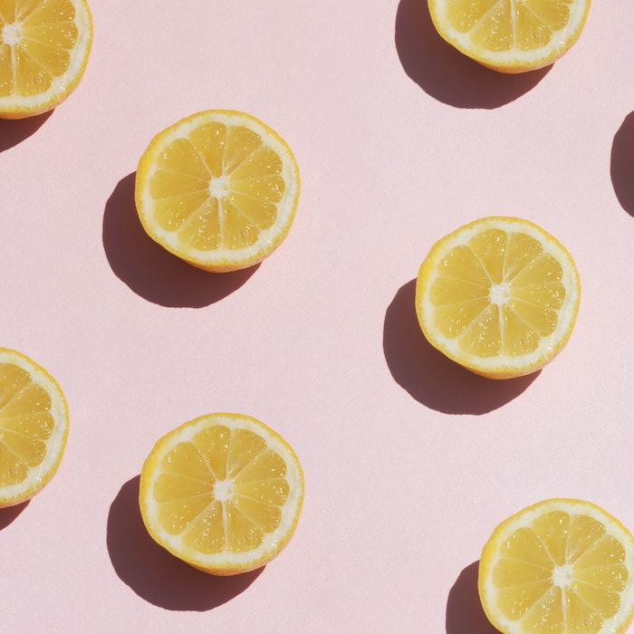 halved lemons arranged symmetrically on pink background best hair mask for dry hair