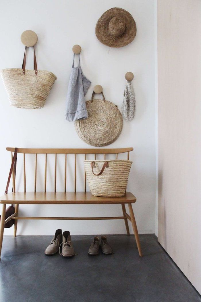hats and bags hanging on white wall above wooden bench placed on black floor entryway decor